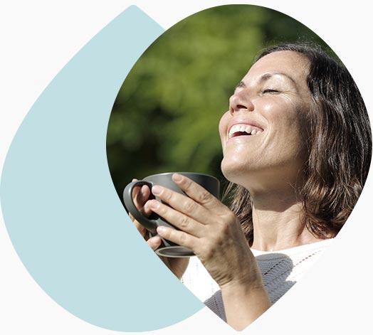 Femme souriante qui boit une infusion