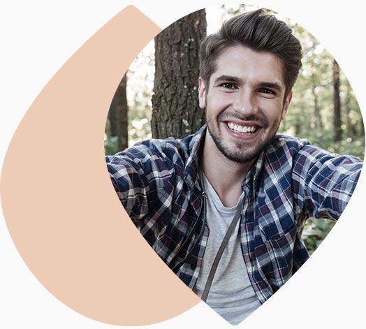 Jeune homme souriant en nature