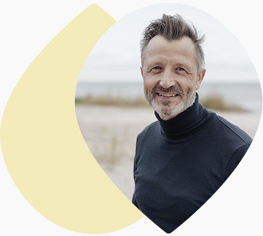 Homme souriant devant la mer