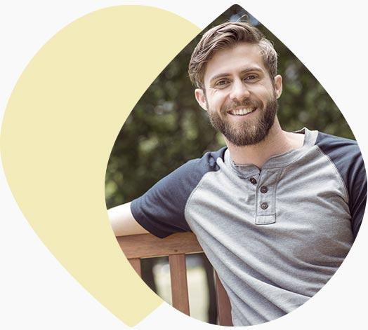 Jeune homme souriant sur un banc