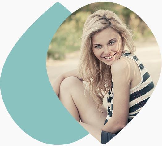 Jeune femme souriante assise sur l'herbe