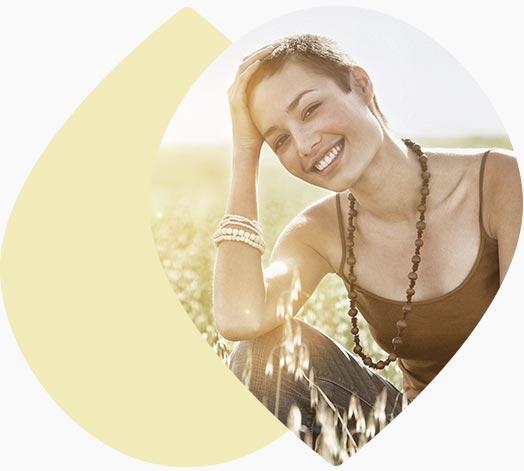 Jeune femme souriante assise dans un champs de blé