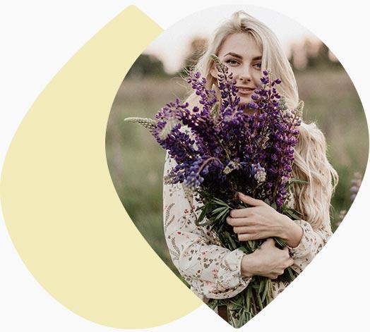 Jeune femme portant un bouquet de lavandes dans un champs