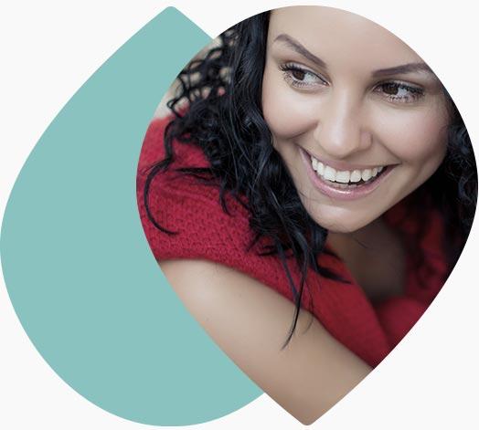 Jeune femme souriante assise par terre