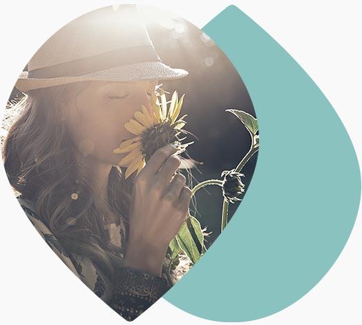 Jeune femme humant une fleur