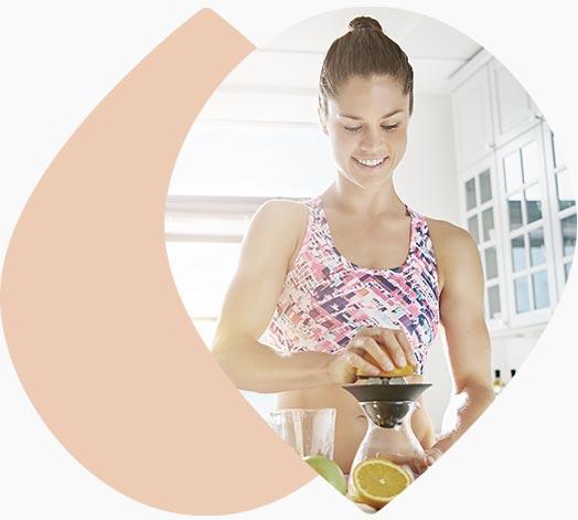 Jeune femme préparant un jus de fruit